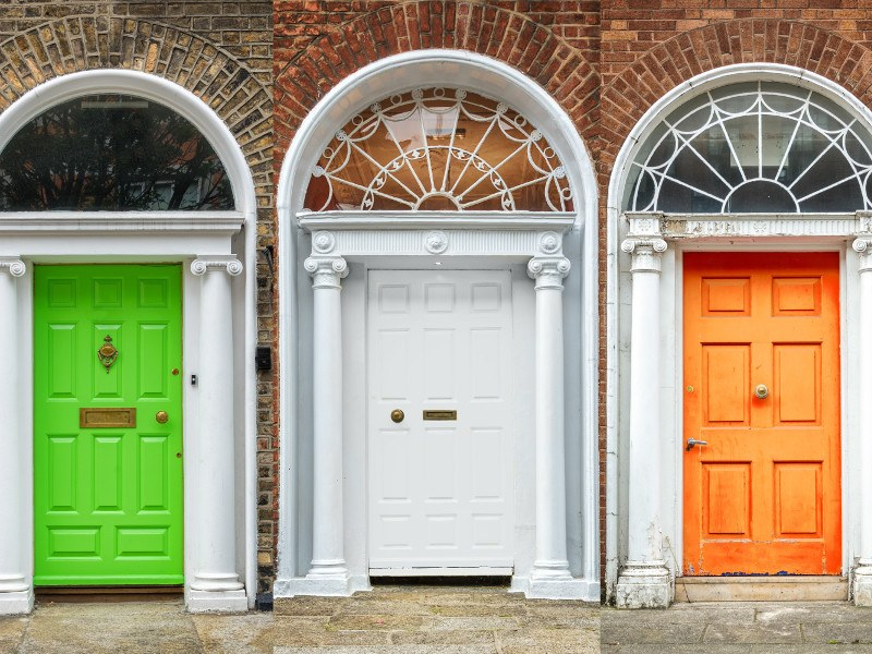 A picture of three georgian doors in dublin painted green, white and gold.