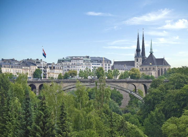 A scenic view of Luxembourg with a bridge surrounded by green forest.