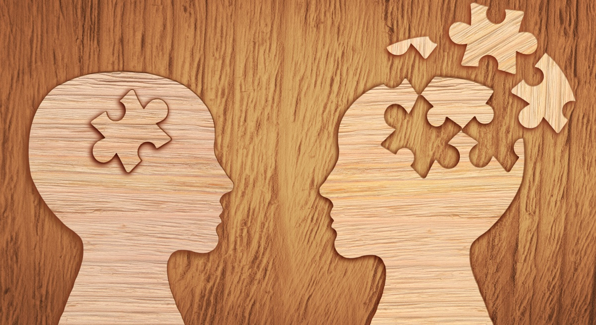 A wooden surface with two wooden heads facing each other. One has broken jigsaw pieces showing poor mental health.