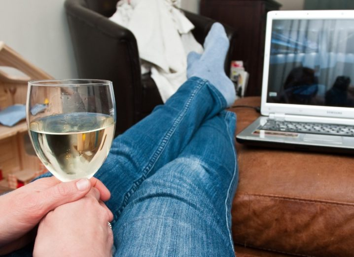 Woman watching Netflix on a laptop with a glass of wine.