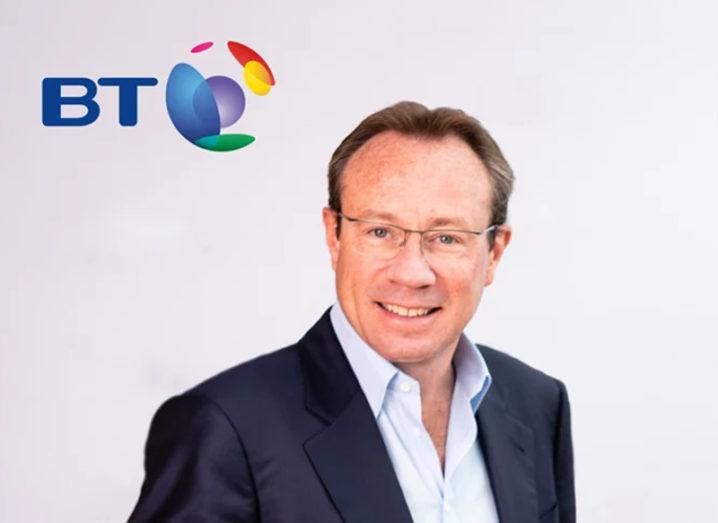 Man in navy jacket and white shirt stands in front of a BT logo.