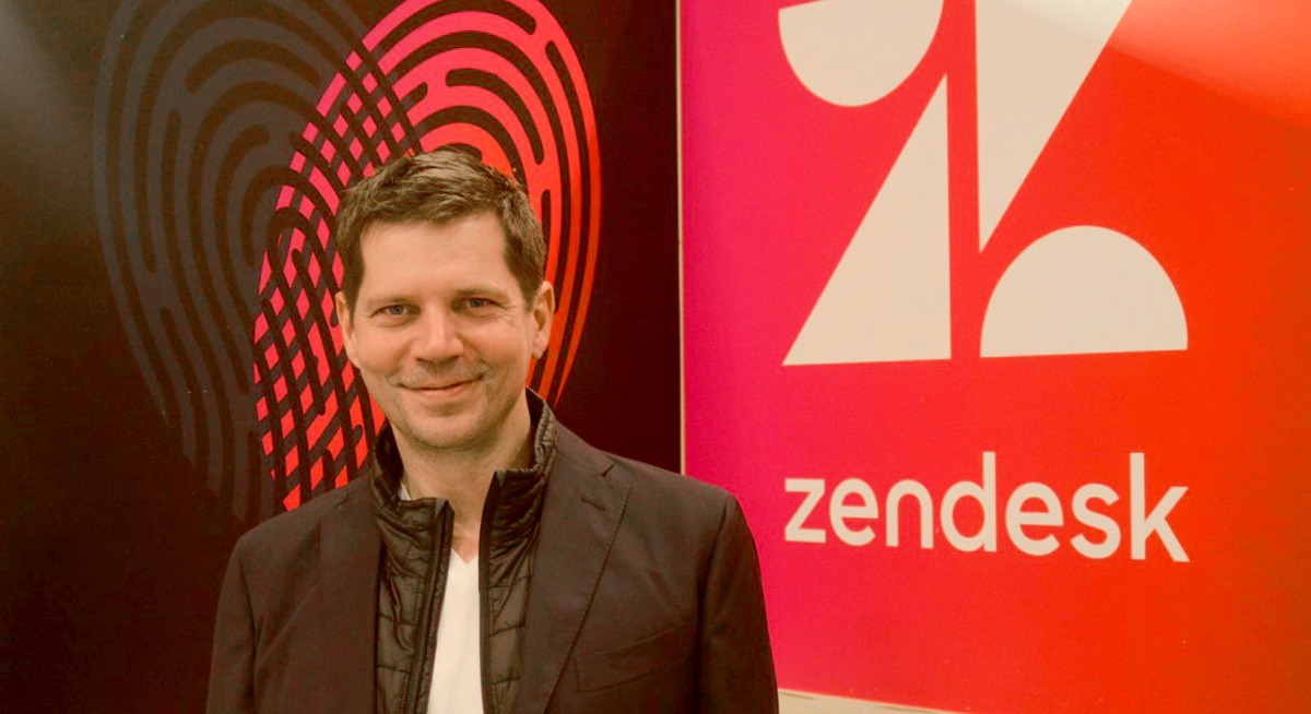 A young man with brown hair smirking into the camera with a red wall emblazoned with the Zendesk logo behind him.