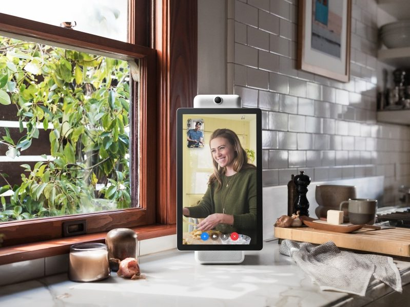 Facebook portal device on a kitchen counter, displaying a woman on a video call.