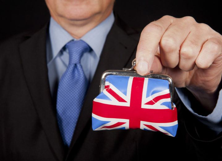 Man in suit with blue tie holds up a little purse emblazoned with the Union Jack.
