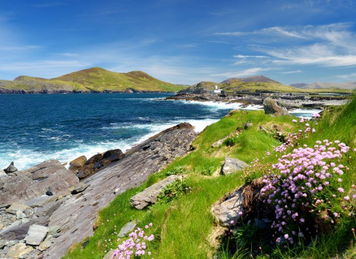 Stunning view of Valentia Island in Kerry, with green grass, jutting rocks and crashing waves in the deep blue sea.