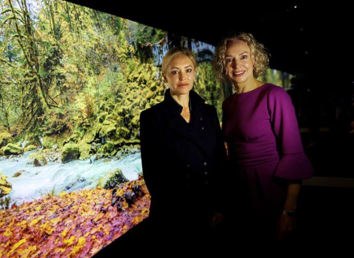Two women with blonde hair stand before a screen showing trees and a stream.