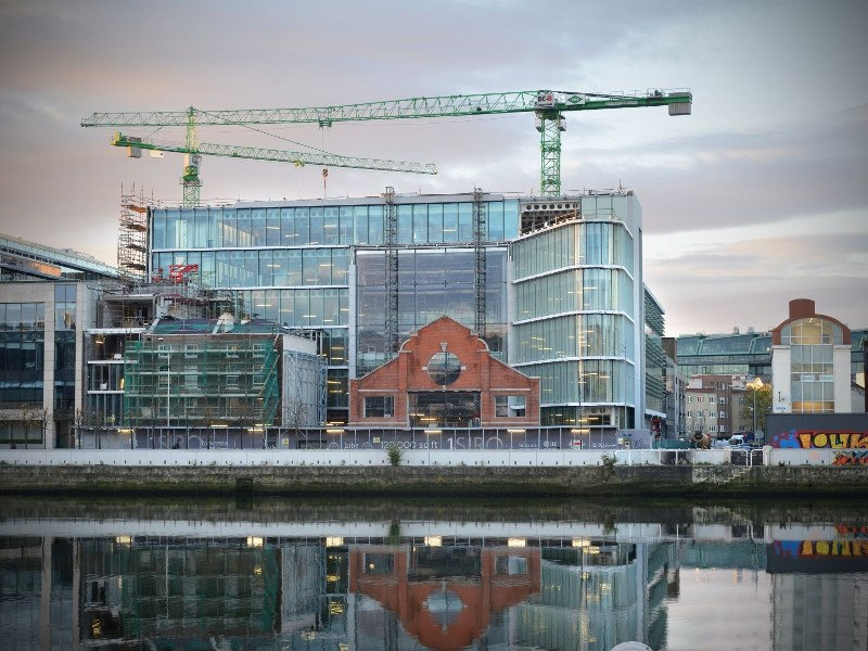 A shiny glass office development with construction towers on south quays of Dublin.