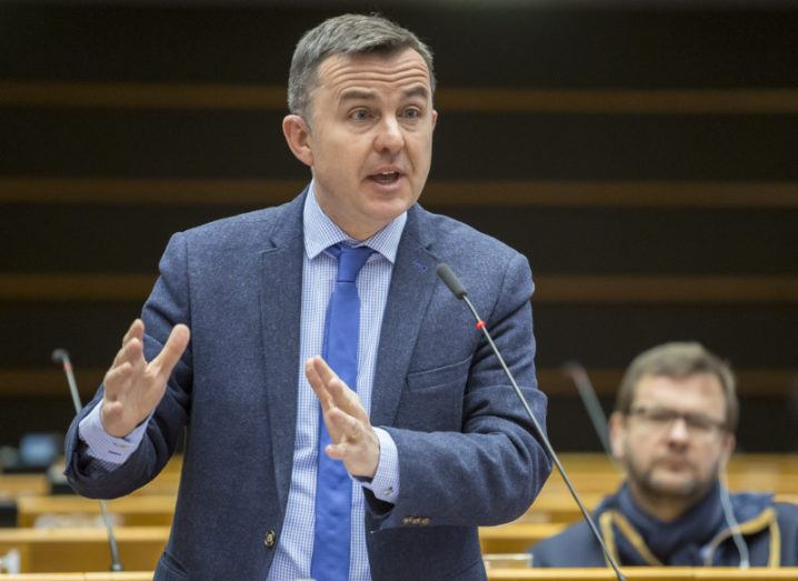 A middle-aged man in a powdery blue suit speaking into microphone with hands raised. He is Fine Gael MEP Brian Hayes.