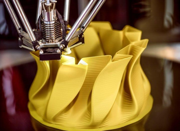 A yellow bowl with folds being 3D printed.