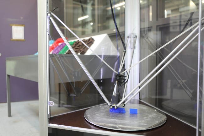 Looking inside a three-sided 3D printer through clear panels as it prints a plastic object.