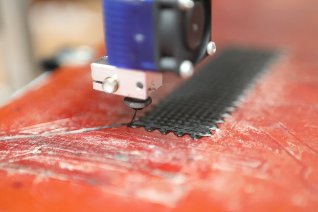 A close-up of a 3D print being constructed layer by layer by extruding the filament from a precise point.