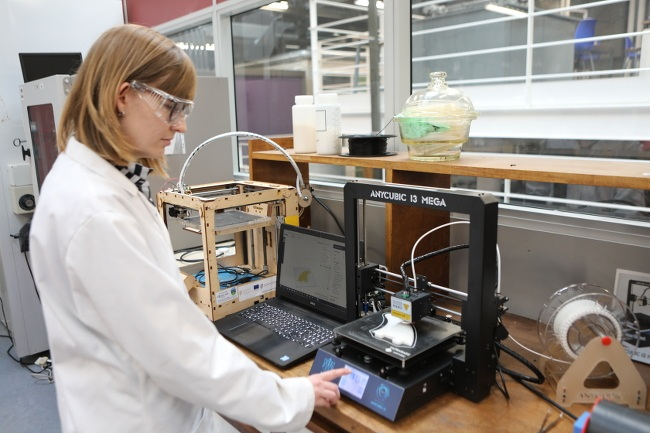 A scientist in lab coat and safety glasses operates the Anycubic 13 Mega 3D printer at a bench.