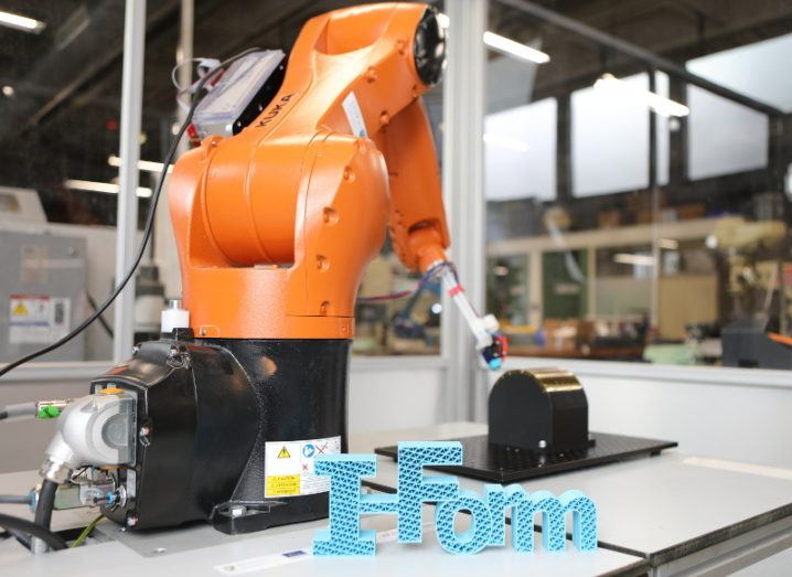 Sky-blue 3D-printed letters spelling 'I-Form' stand before a large orange robotic arm.