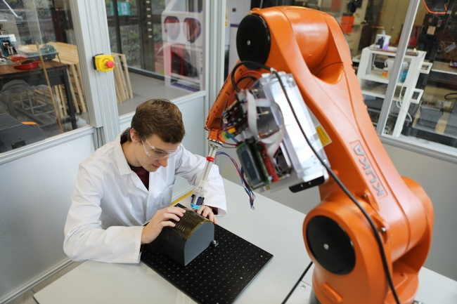 Overhead view of an orange robotic arm printing onto a surface held by a scientist in lab coat and safety glasses.