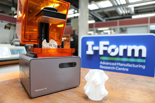 Three-dimensional I-Form logo behind a FormLabs 3D printer and a 3D-printed object.