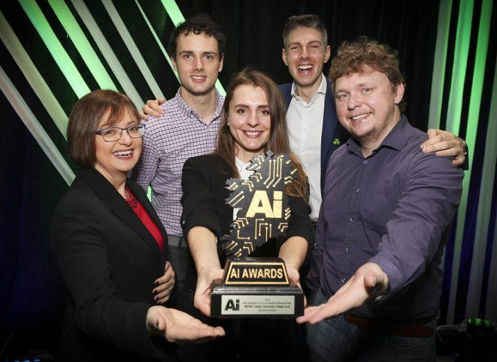 AI Award winners holding one of the trophies against a black and green striped background.