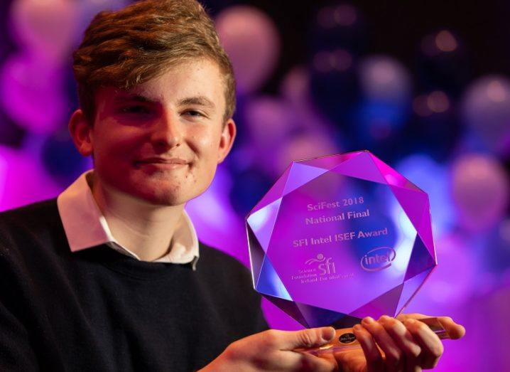 A smiling Adam Kelly holding his SciFest 2018 glass trophy against a purple background.