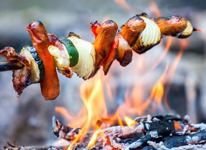 A kebab stick loaded with sausages, courgette slices and onion wedges roasts over an open fire.