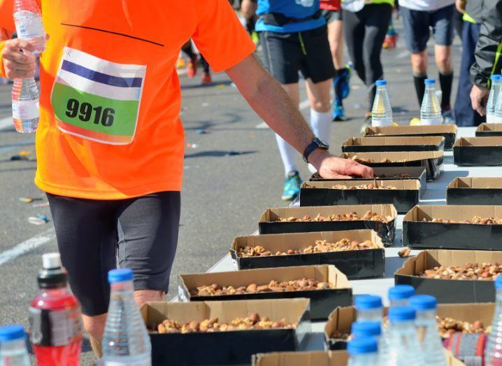 A male runner in an orange t-shirt stops to grab a snack in the middle of a run.