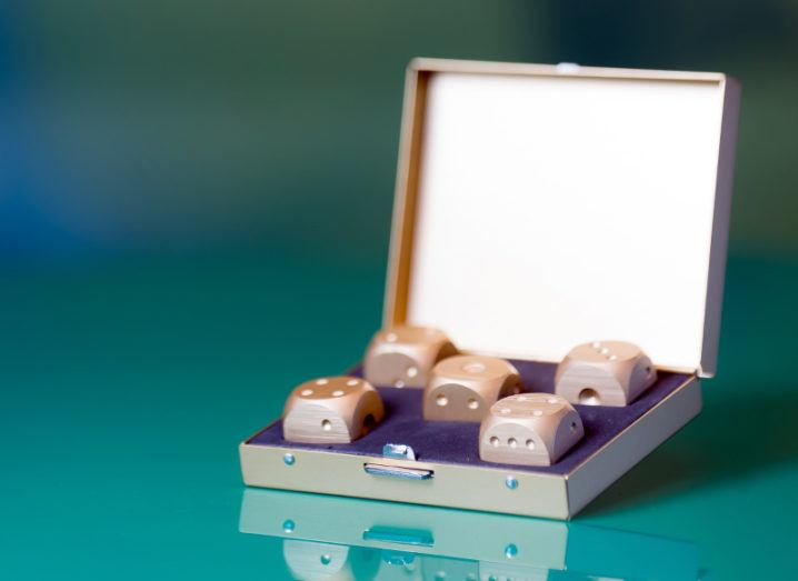 A slim hinged box opened wide to reveal five dice set in purple velvet casing.