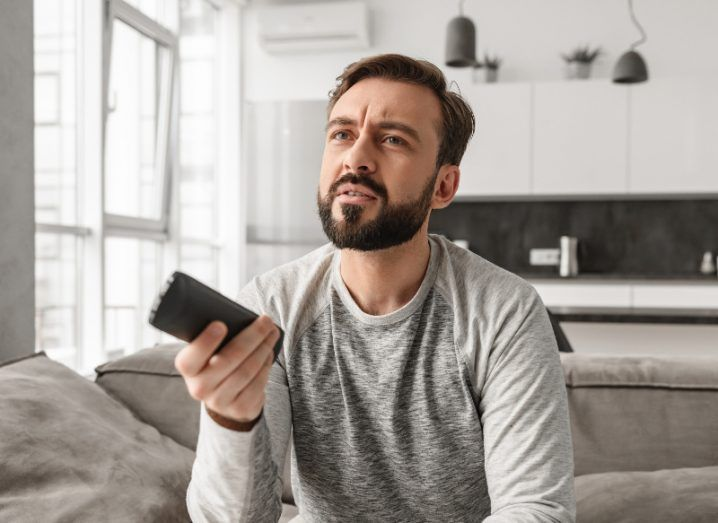 man in grey long-sleeved top holding remote and looking confused at the tv.