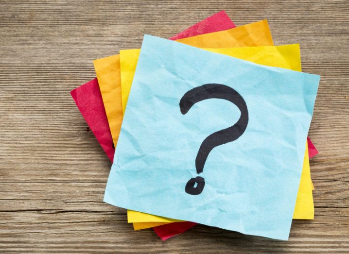 A stack of colourful sticky notes and on the top one is drawn a question mark.