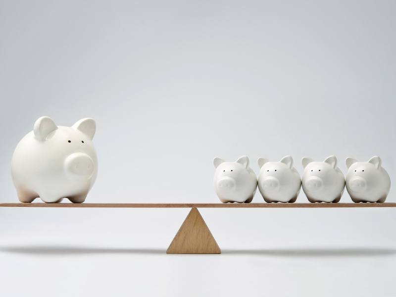 A see-saw balanced equally with one large white ceramic piggy bank on one end and four smaller piggy banks on the other.