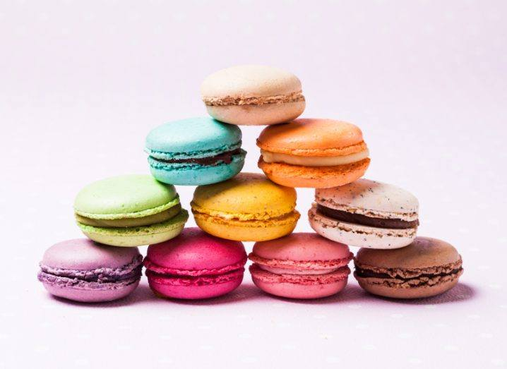 A pyramid of 10 carefully balanced macaroons, each one a different colour, against a soft pink background.