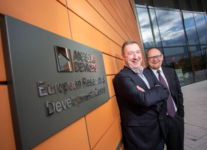 Two middle-aged men in suits, one bald and with glasses, the other with grey slicked back hair, smiling at camera against a backdrop of a plague emblazoned Analog Devices European Research and development centre.