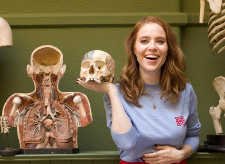 A red-haired woman laughs as she holds a model skull in one hand, standing next to human anatomy model.