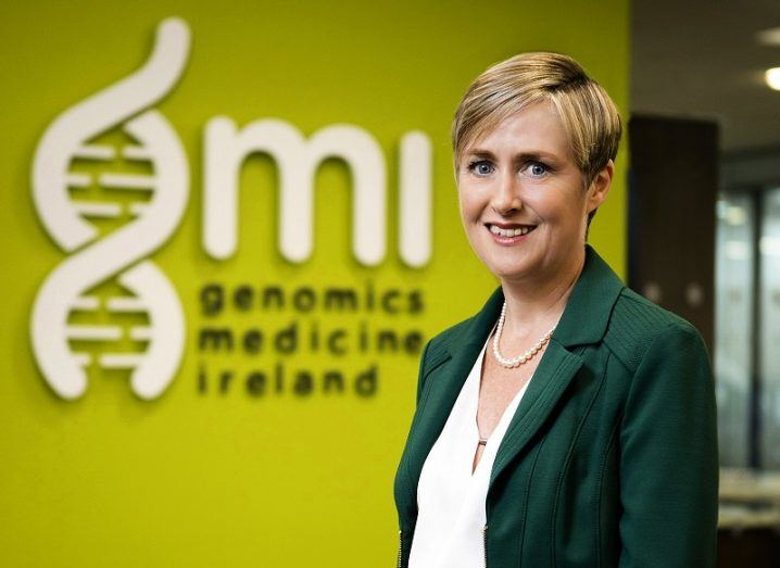 Dr Anne Jones in a dark green blazer in front of the green and white background sign of GMI.
