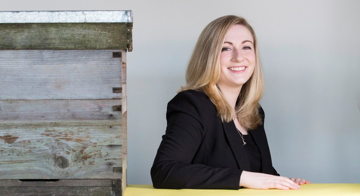 Smiling woman with blonde hair and black jacket beside a bee hive.