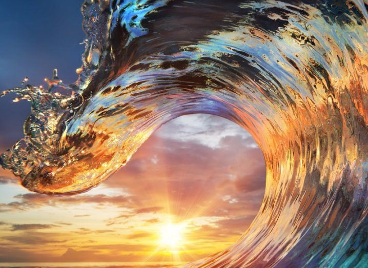 Large, colourful ocean wave against backdrop of a setting sun.