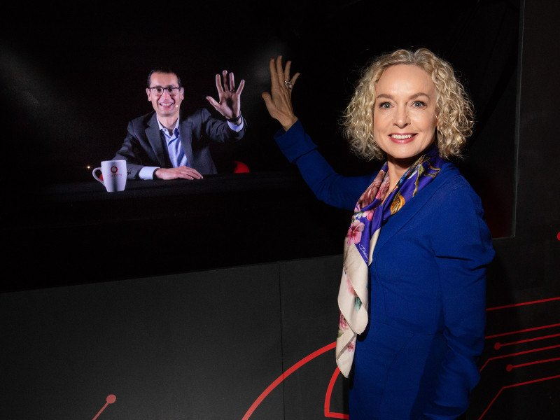Woman with blonde hair stands before a holographic screen communicating to a man on the screen.