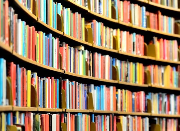 Books of many different colours on a rounded book shelf.