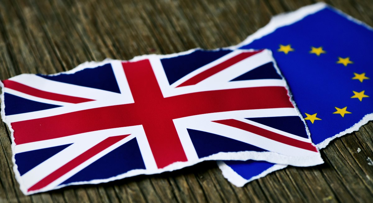 Two torn pieces of paper, one showing the UK flag, the other showing the EU flag on a wooden table, representing Brexit.