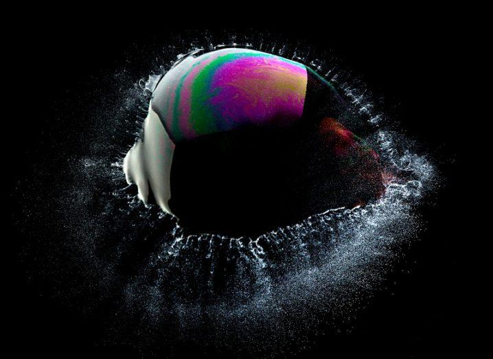 Colourful bursting bubble against a black background.