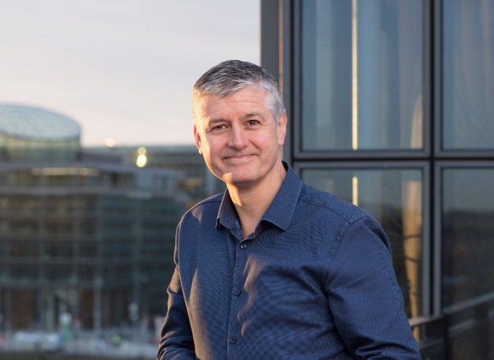 middle aged man with grey hair wearing dark blue shirt and smiling, standing outside on balcony, with setting sun and city landscape in background.