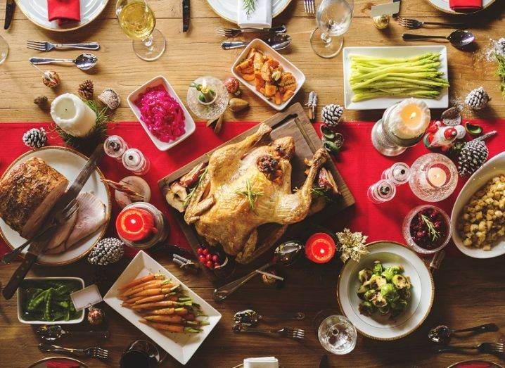 Turkey and other food spread across a wooden table for Christmas dinner.
