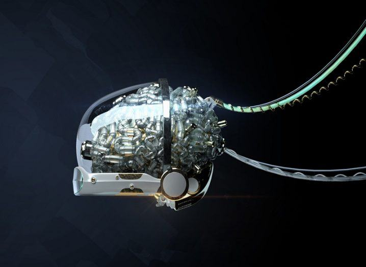 Abstract shot of a computerised brain in a glass casing hooked up to cables.