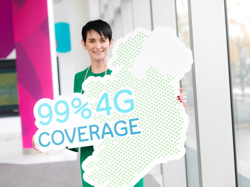 Woman with black hair and green dress holds an image of Ireland with the words 99pc 4G coverage.