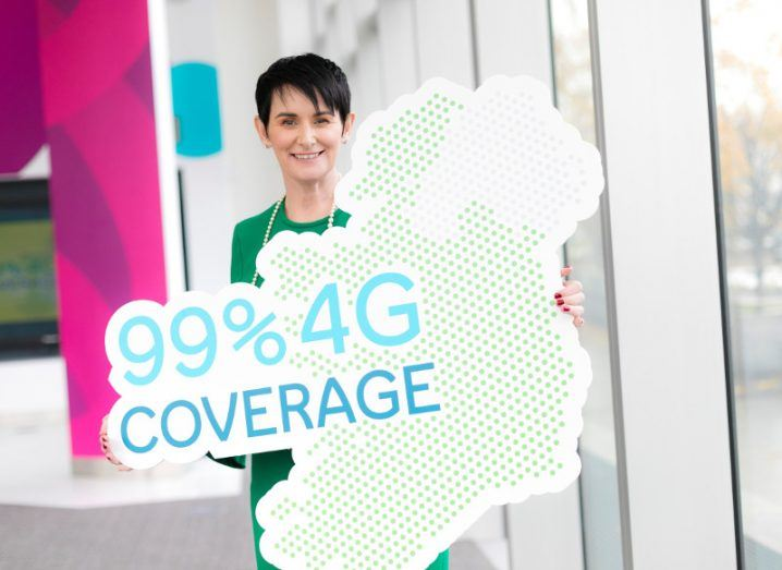 Woman with black hair and green dress holds a sign in shape of Ireland with words 99 per cent 4G coverage.