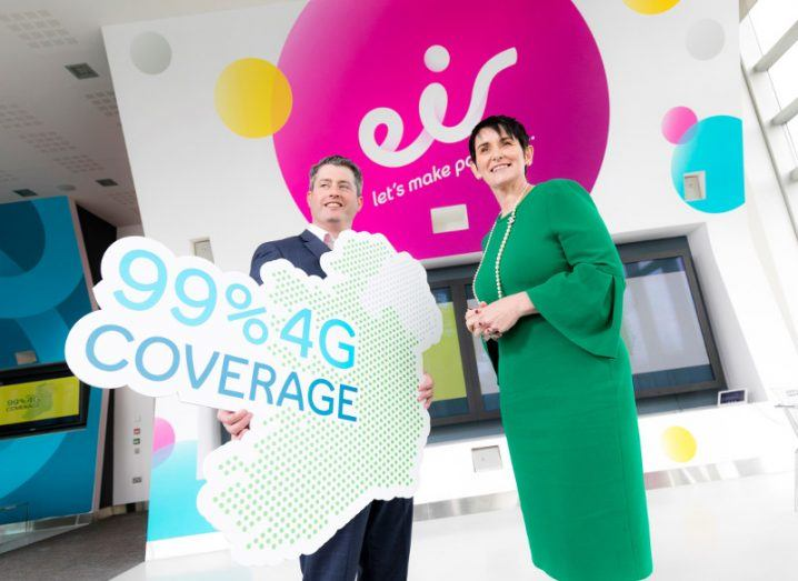 Man in suit with woman in green dress holding a sign saying 99 per cent 4G coverage in front of bright pink Eir logo.