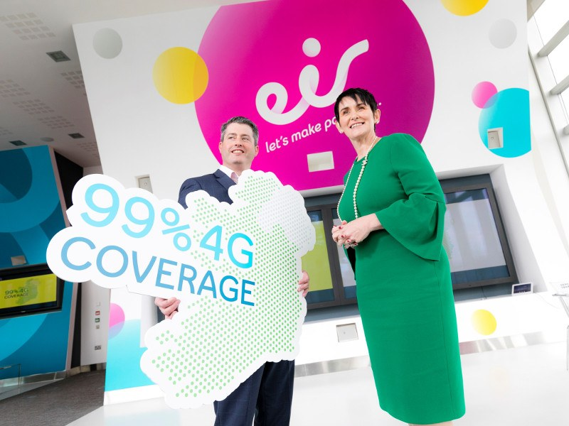 Man in suit with woman in green dress holding a sign saying 99 per cent 4G coverage.