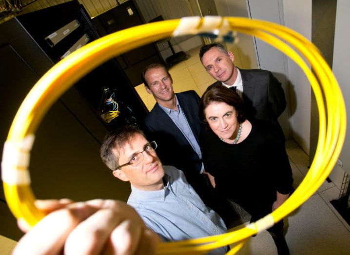 Three men and a woman hold up a yellow fibre optic cable.