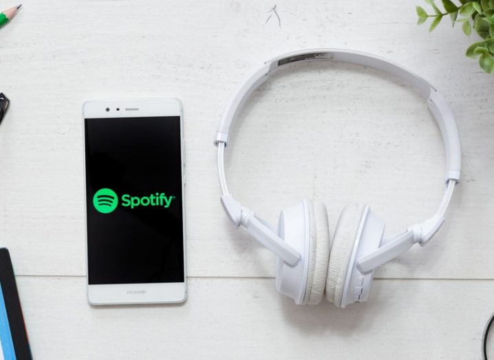 A pair of headphones on a white table beside a smartphone displaying the Spotify logo.