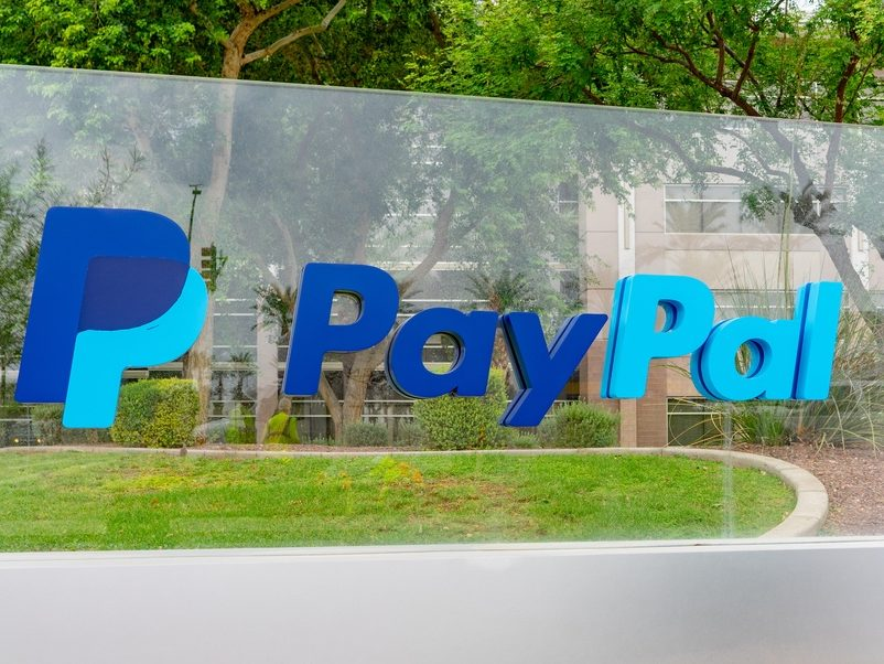 The PayPal logo on a glass panel outside an office in Arizona, with trees in the background.