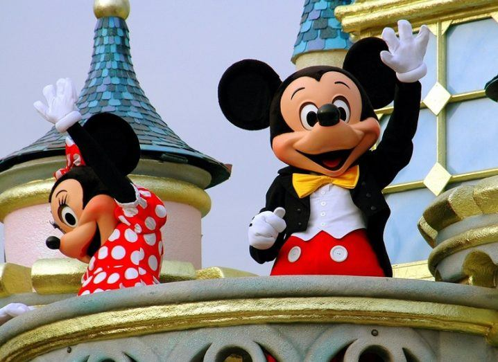 Mickey and Minnie Mouse waving to crowds from the Magic Kingdom castle in Hong Kong.