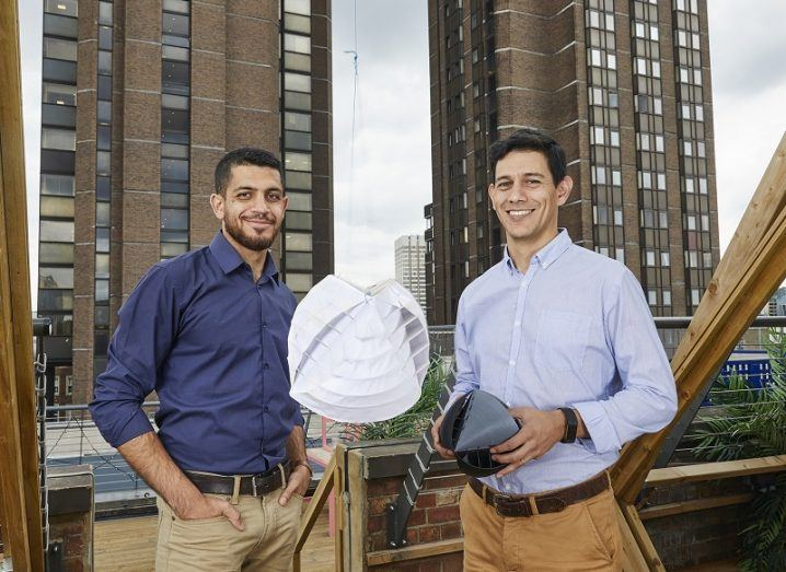 Wind turbine designers Nicolas Orellana and Yaseen Noorani holding their creation against backdrop of apartment blocks.