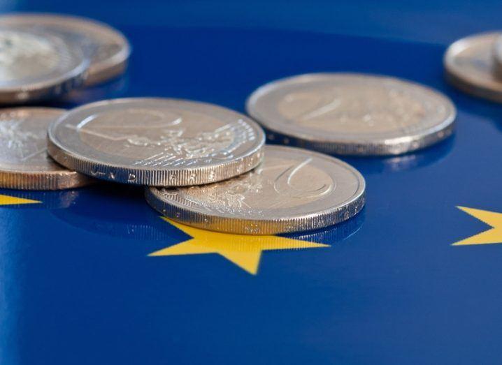 Image of euro coins on a European flag.